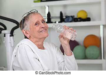 Una anciana bebiendo agua embotellada en un gimnasio