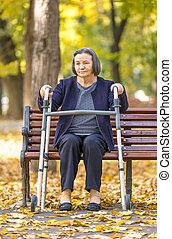 Una anciana con caminante al aire libre