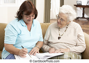 Una anciana en discusión con un visitante de salud en casa
