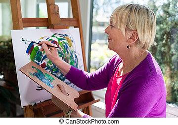 Una anciana feliz pintando para divertirse en casa
