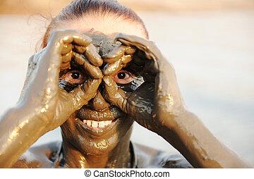Una anciana que disfruta del lodo natural de los minerales en la cara que proviene del mar muerto en el fondo