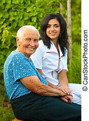 Una anciana sonriente al aire libre con un médico y una enfermera