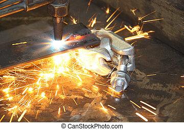 Una antorcha de acetileno cortando un pedazo de acero mostrando manchas de metal caliente