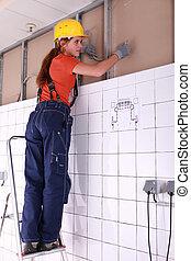 Una artesanía femenina instalando sistemas de cableado