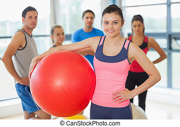 Una bola de ejercicios con clase de gimnasia en el fondo