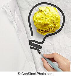 Una bombilla dibujante en papel arrugado como concepto creativo
