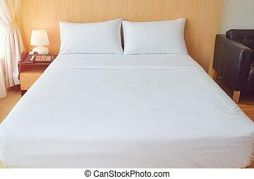 Una cómoda cama blanca en la habitación para muebles cómodos y ropa