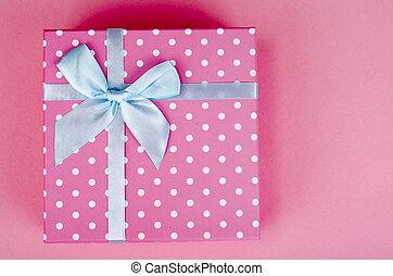 Una caja cuadrada de lunares rosados de fondo brillante