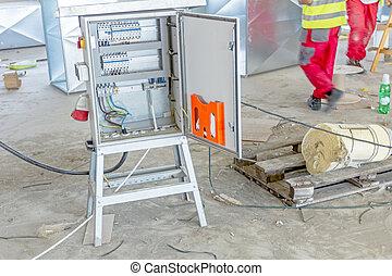 Una caja de distribución de electricidad con cables y interruptores de circuitos, una caja de fusibles en la construcción