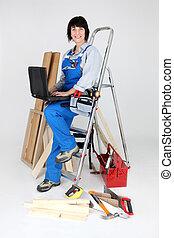 Una carpintera con escalera y portátil