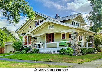 Una casa de artesanos verdes con porche cubierto.