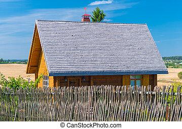 Una casa de madera con una cerca en el pueblo