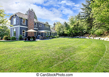 Una casa grande azul con jardín y un paisaje verde.