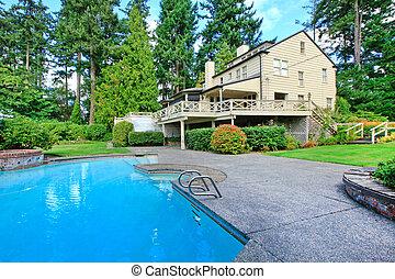 Una casa marrón grande con jardín de verano y piscina