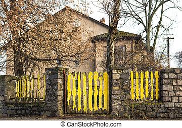 Una casa vieja con una cerca amarilla
