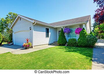 Una casita blanca con flores.