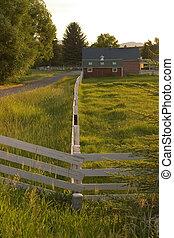Una cerca de campo que lleva a un rancho
