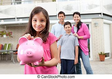 Una chica ahorrando dinero con una familia atrás