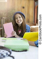 Una chica alegre y sonriente con un libro