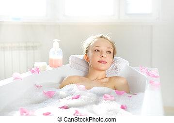 Una chica atractiva que se relaja en el baño