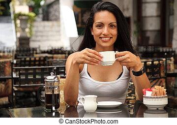 Una chica bebiendo café en el café
