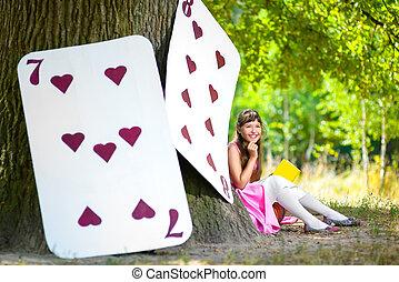 Una chica cerca de las grandes cartas bajo un enorme roble. Alice en el concepto de Wonderland