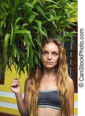 Una chica cerca de un arbusto de orquídeas