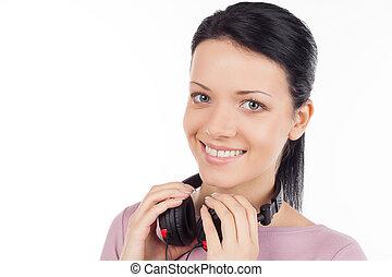 Una chica con auriculares. Hermosa joven sosteniendo auriculares y sonriendo mientras está aislada en blanco