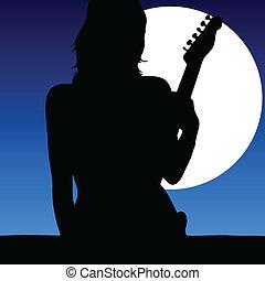 Una chica con guitarra a la luz de la luna