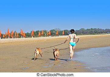 Una chica con perros corriendo por la playa
