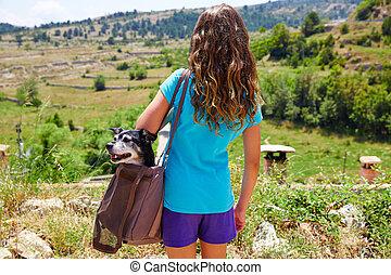 Una chica con un perro en una bolsa mirando montañas