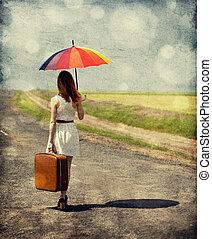 Una chica de moda joven con paraguas y valija al aire libre. Foto con bokeh retro en el fondo.