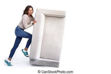 Una chica empujando un sofá viejo