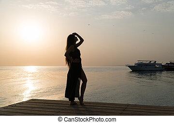 Una chica en traje de baño y una capa está parada en el muelle y se encuentra con el amanecer