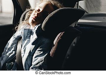 Una chica encantadora de siete años durmiendo en un asiento para niños