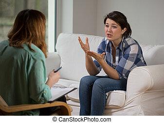 Una chica gesticulando hablando con un psicólogo