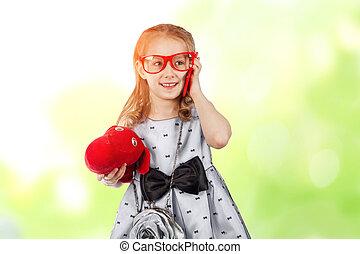 Una chica glamorosa con gafas rojas y un perro hablando por teléfono