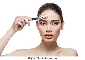 Una chica hermosa que aplica cimientos con cepillo