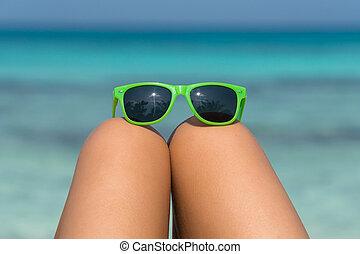 Una chica joven en una playa con gafas en las piernas