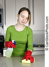 Una chica limpiando la cocina