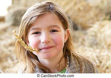 Una chica linda sonriendo con paja en la boca