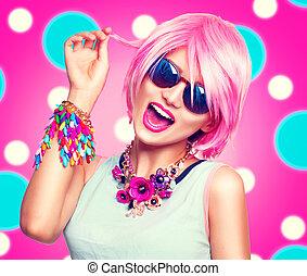Una chica modelo adolescente con cabello rosa, accesorios coloridos y gafas de sol
