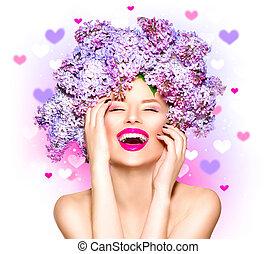 Una chica modelo de belleza con peinado de flores lilas