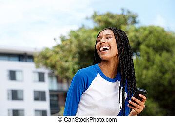 Una chica negra genial riéndose fuera con el móvil