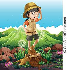 Una chica parada sobre el muñón cruzando las montañas