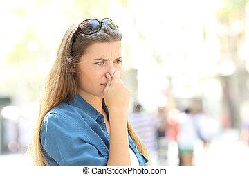 Una chica que se tapa la nariz por mal olor