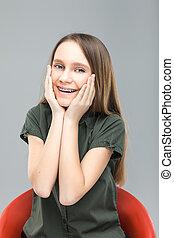 Una chica rubia con frenos riéndose