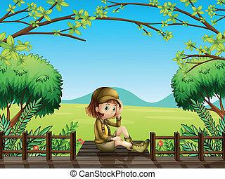 Una chica sentada en el puente de madera