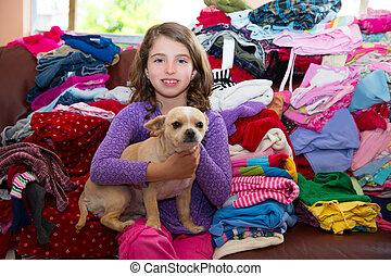 Una chica sentada en un sofá sucio con un perro chihuahua