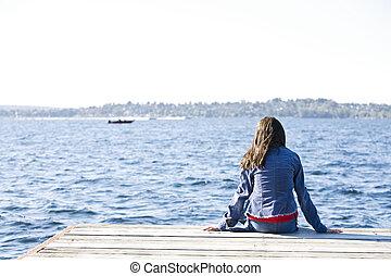 Una chica sentada sola en el muelle del lago, mirando hacia el agua.
